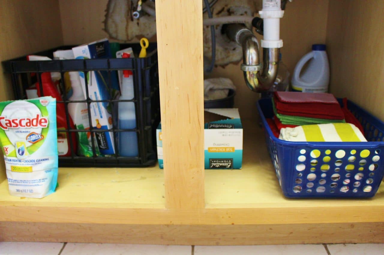 No drawers? No problem! Use plastic baskets to store your kitchen towels, which can also be found at the dollar store! You can also keep your cleaning supplies organized with a plastic crate.